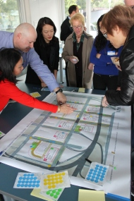 (left-right) Barbara Inaba, Stuart Lerner, Jane Kim, Katy Lidell, place stickers to rank the importance of changes need on a map of down town San francisco during a Community Public Works meeting Monday night at South Harbor in San Francisco CA, Photographed by Katie Sanders.