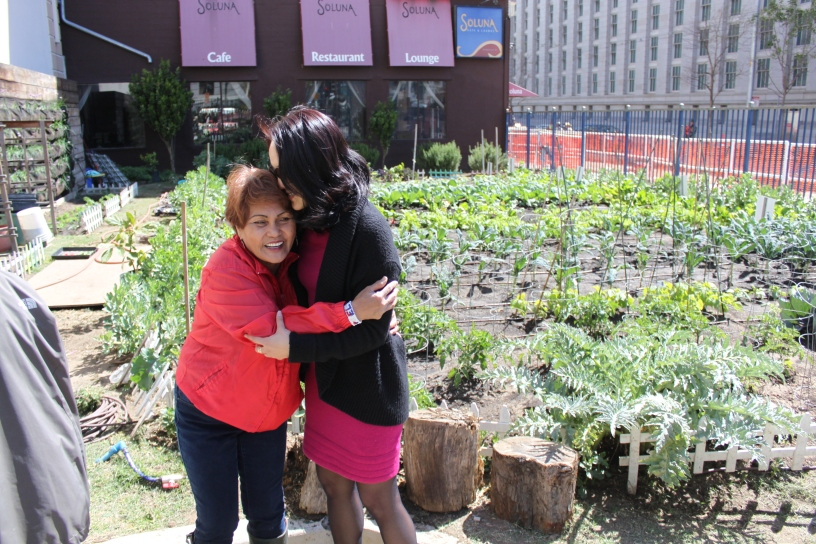 Jane Kim hugs her friend Nella (last name unknown) who works in the garden for the people of the tenderloin district in SF. Nella and other volunteers harvest the vegetables such as chard greens, Kale, and Tomatoes and give them to over 200 people who can't afford vegetables. last Tuesday 4/14/15 photo by Katie Sanders
