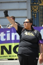 """Tracy Ferguson holds her fist in the air to protest against the death of people of black and brown colors by police. the Black lives matter protest took place on the steps of City Hall as part of the """"Shut Down SF"""" event that took place across the city by various groups protesting against police brutality. Tuesday the 14th of April photo by Katie Sanders"""