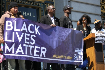 """Alisha brown(far right) speaks while Protestors (Names Unknown) hold signs for the Black lives matter protest on the steps of City Hall as part of the """"Shut Down SF"""" event that took place across the city by various groups protesting against police brutality. Tuesday the 14th of April photo by Katie Sanders"""