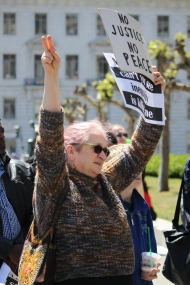 """Molly Hankwitz holds up a No Justice No Peace sign in protest of violence against the death of people of black and brown colors by police. the Black lives matter protest took place on the steps of City Hall as part of the """"Shut Down SF"""" event that took place across the city by various groups protesting against police brutality. Tuesday the 14th of April photo by Katie Sanders"""